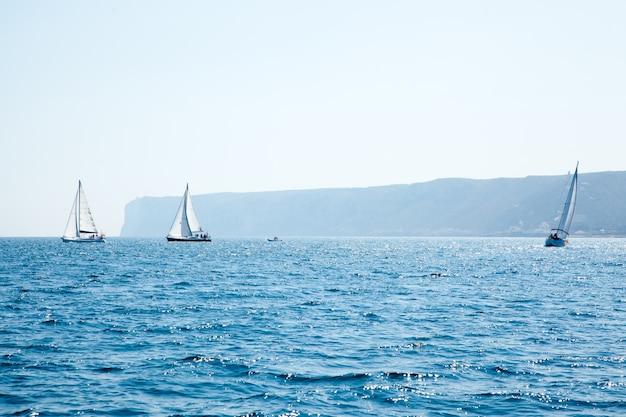 Los barcos navegan regata con veleros en mediterráneo.