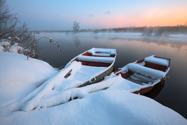 Barcos en la nieve en el río en invierno