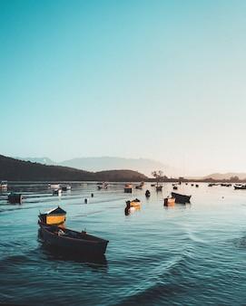 Barcos de pesca en el agua en el mar con hermoso cielo azul claro