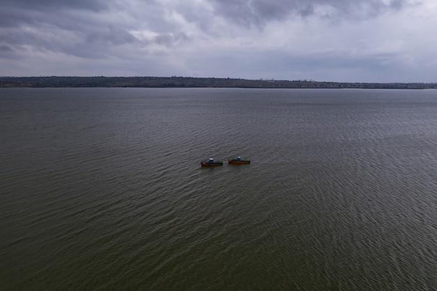 Barcos de pesca, flotando en las tranquilas aguas y yendo a pescar bajo un cielo con nubes