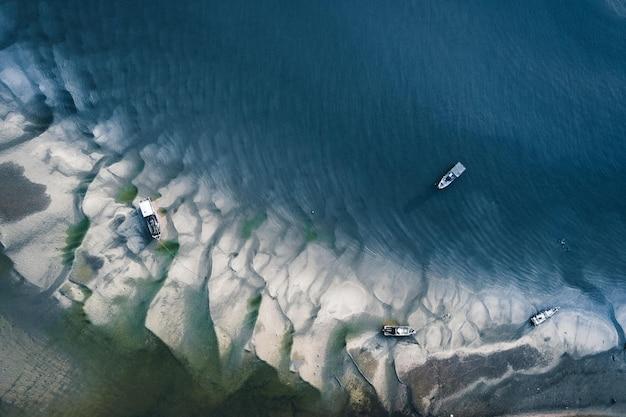 Barcos de pesca en la superficie del agua clara con rocas bajo el agua