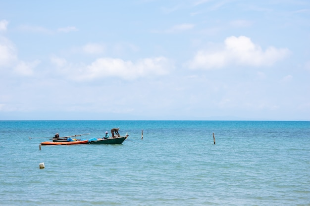 Barcos de pescadores locales en el lado izquierdo flotando sobre el mar con un cielo brillante en el fondo