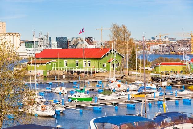 Barcos en el puerto con almacén y ciudad de oslo en el fondo