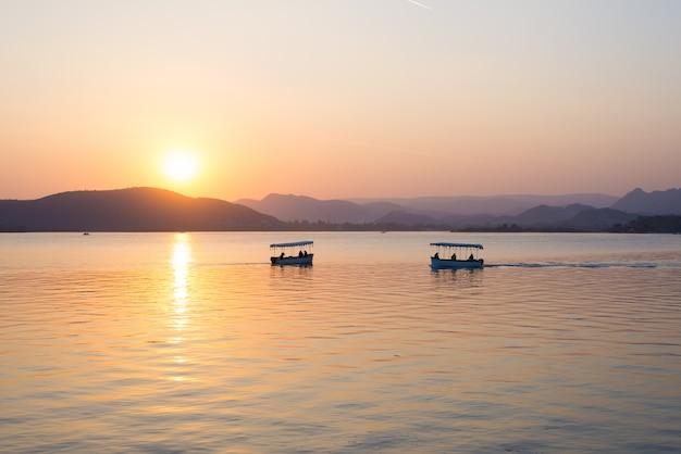 Los barcos que flotan en el lago pichola con una colorida puesta de sol se reflejan en el agua más allá de las colinas. udaipur, rajasthan, india.