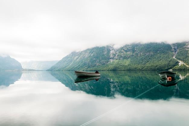 Barcos solitarios en un lago tranquilo con montaña brumosa en el fondo