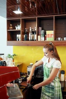 Barista apisonadora de café en portafiltro