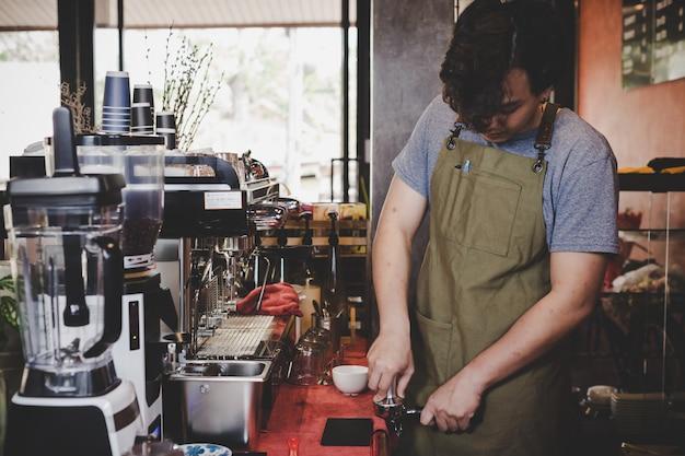 Barista asia que prepara la taza de café para el cliente en cafetería.