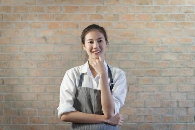 Barista asiático apuesto joven que se coloca en cafetería con la pared de ladrillo hermosa en fondo.