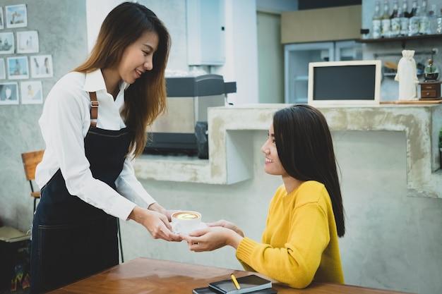 Barista asiático que sirve una taza de café al cliente