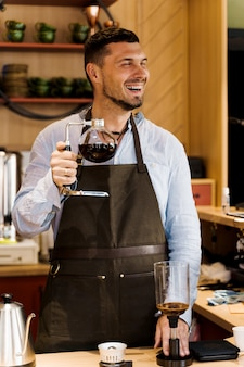 Barista bromea y sonríe con café sifón en café