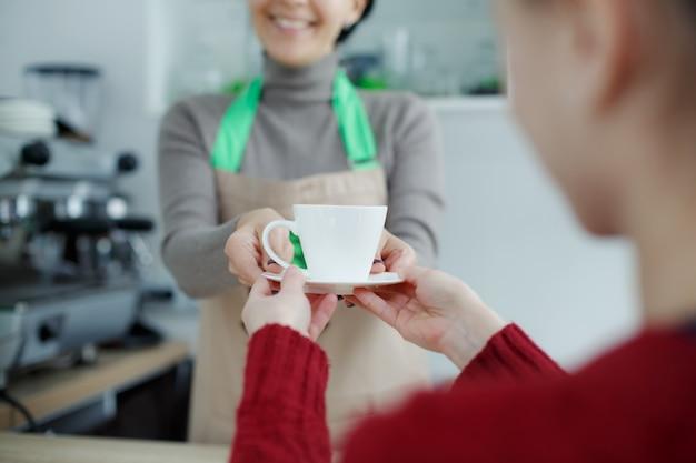 Barista en delantal en cafetería ofrece café recién preparado al cliente