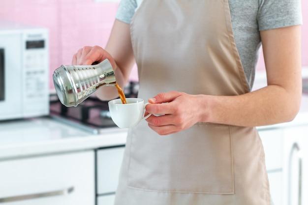 Barista en delantal preparando café turco sabroso caliente de cezve