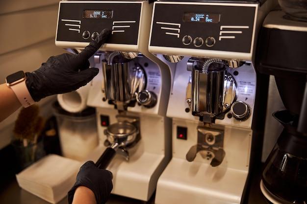 Barista experimentado con molinillo de café moderno en el trabajo