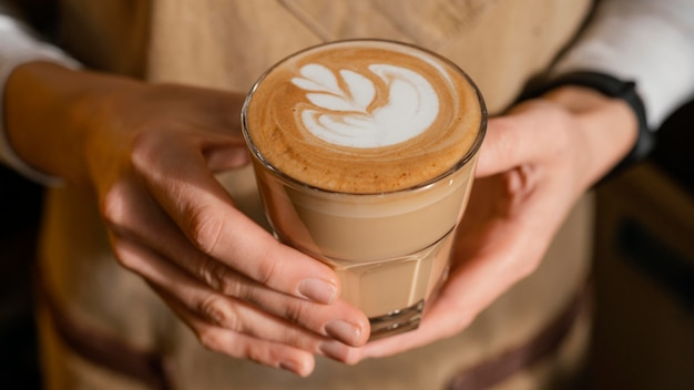 Barista femenina con delantal sosteniendo un vaso de café decorado