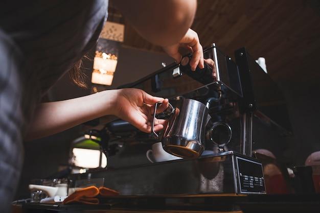 Barista femenina prepara café expreso de una máquina de café en la cafetería.