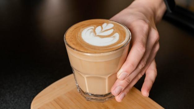 Barista femenina sosteniendo un vaso de café decorado