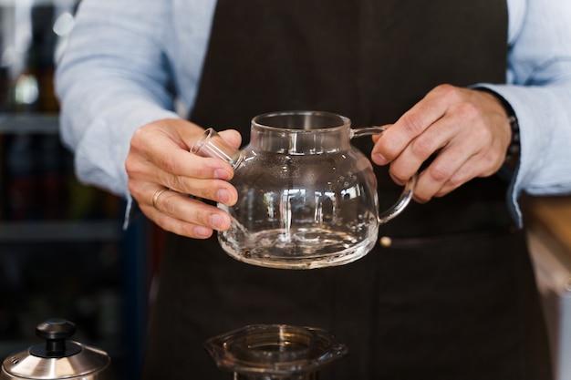 Barista gira en manos y mira la cafetera con café antes de hacer aeropress