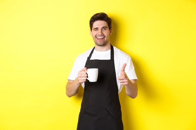 Barista guapo en delantal negro sosteniendo la taza de café, señalando con el dedo, invitando a visitar café, de pie sobre fondo amarillo