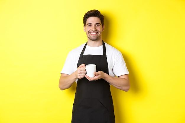 Barista guapo que sirve café, trae taza, de pie con delantal negro con una sonrisa amistosa.