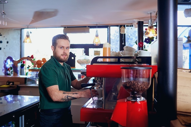Barista hace una bebida caliente en la máquina de café en el bar.