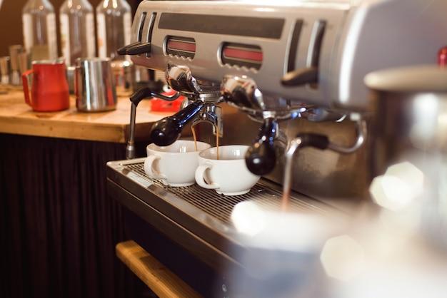 Barista hacer café con leche arte con máquina de café espresso en la cafetería.