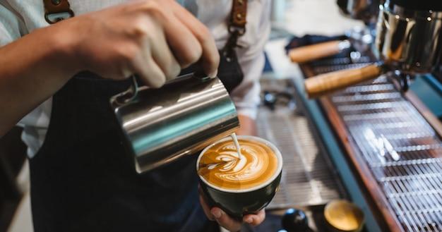Barista haciendo arte latte, foco de disparo en una taza de leche y café