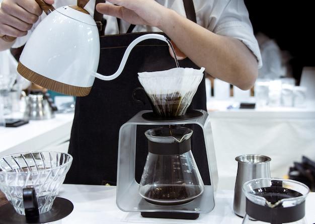 Barista haciendo café, barista vertiendo café en vaso.
