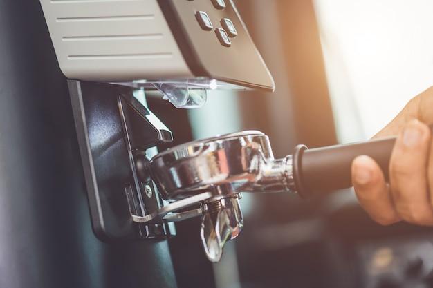 Barista haciendo café moliendo granos de café recién tostados con máquina