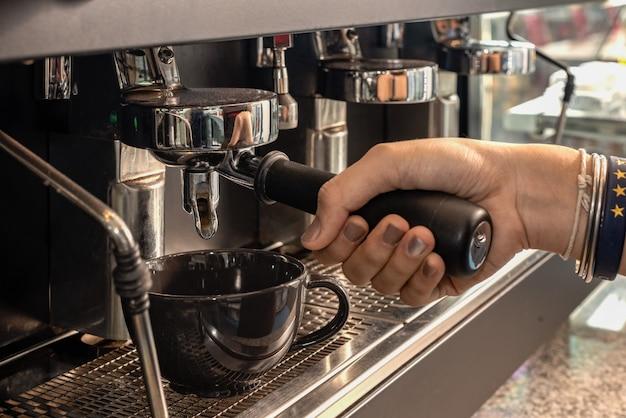 Barista haciendo capuchino con cafetera espresso en cafetería