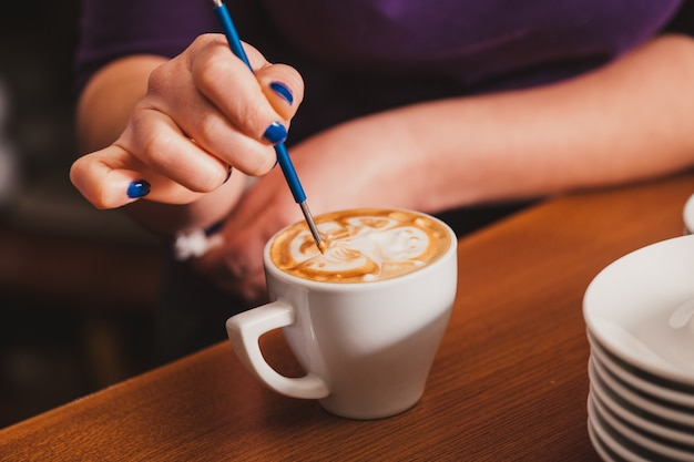 Barista haciendo una taza de café latte art con un dispositivo de metal especial - latte-art pen tool