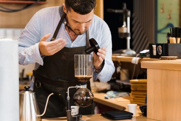 Barista huele café aromatizado en un dispositivo de sifón