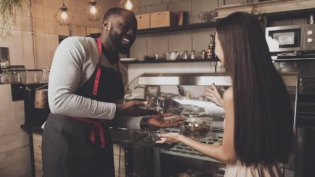 Barista macho ayuda a una chica a elegir un postre.