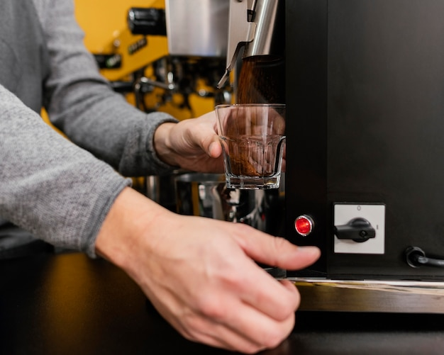 Barista macho moliendo café en la cafetería.