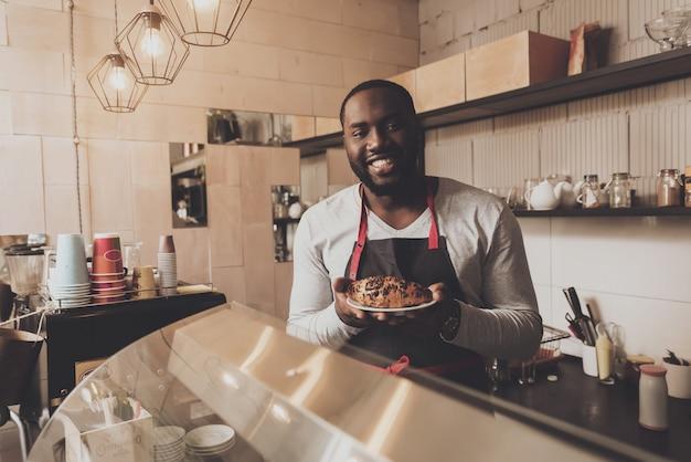 Barista macho sirve un croissant ordenado al cliente.