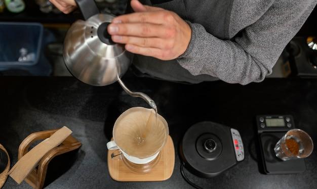 Barista macho vertiendo agua hirviendo en el filtro de café