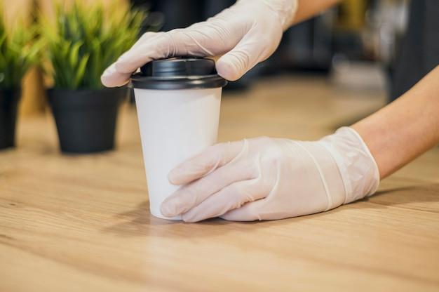 Barista manejando la taza de café con guantes de látex
