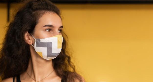 Barista con una máscara médica en la cafetería con espacio de copia