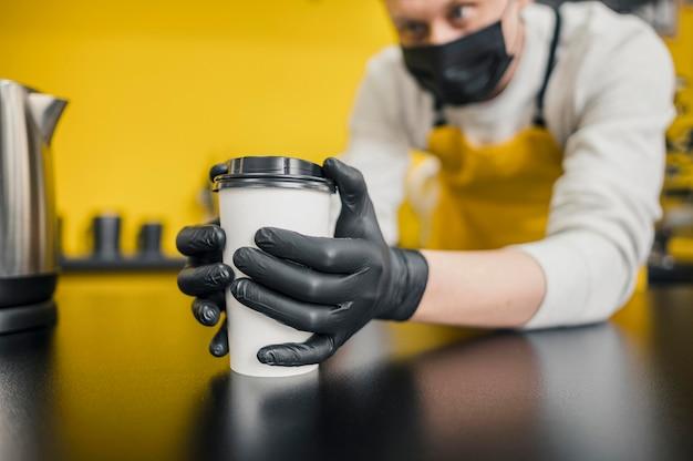 Barista con máscara médica y guantes con taza de café
