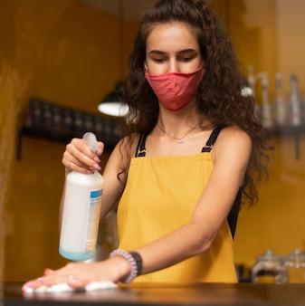 Barista con una máscara médica mientras limpia en la cafetería.