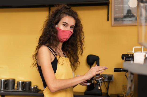 Barista con una máscara médica mientras prepara café