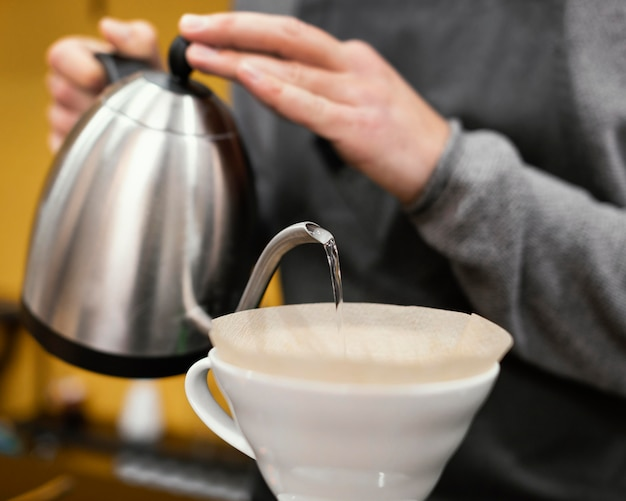 Barista masculino con delantal vertiendo agua en el filtro de café