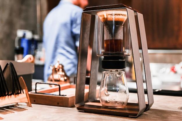 Barista masculino haciendo café vertido con un método alternativo llamado goteo. ciérrese encima del molinillo de café moderno.