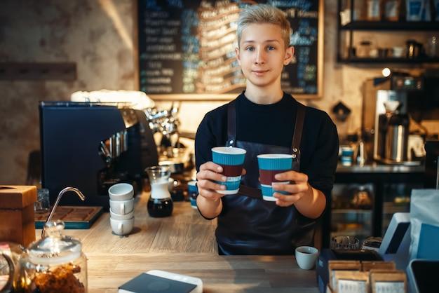 Barista masculino tiene dos tazas de café caliente recién hecho
