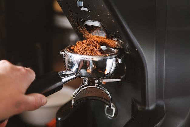 Barista moliendo los granos de café con máquina de café