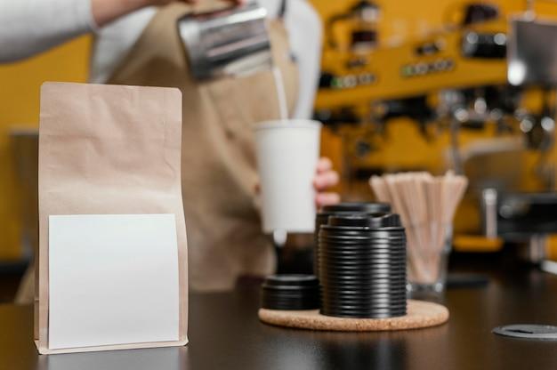 Barista mujer defocused vertiendo leche en la taza de café