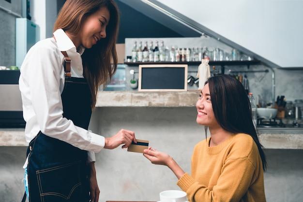Barista de la mujer que sostiene el café para ir taza y tarjeta de crédito, camarera de sexo femenino de asia que usa el pago sin contacto