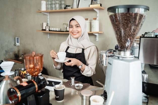 Barista mujer sonriendo cuando se paran en la cafetería pub