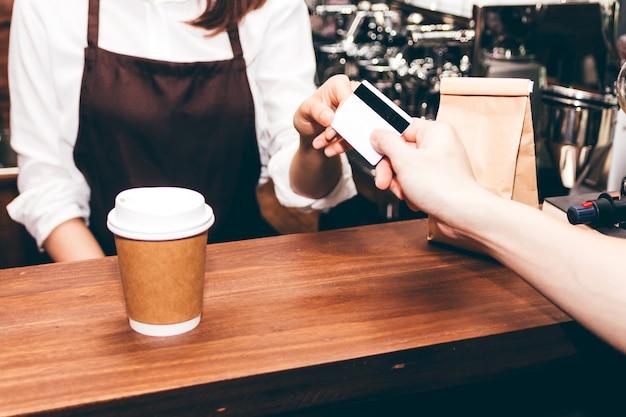 Barista mujer tomando una tarjeta de crédito del cliente en la cafetería