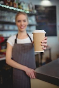 Barista ofreciendo una taza de café en la cafetería.