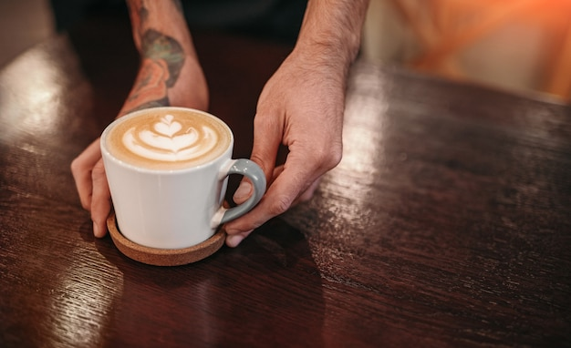 Barista poniendo café recién hecho en el mostrador